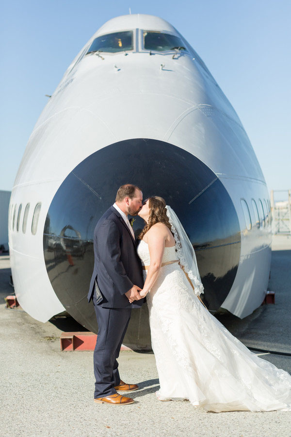 bride and groom kiss in front of airplane