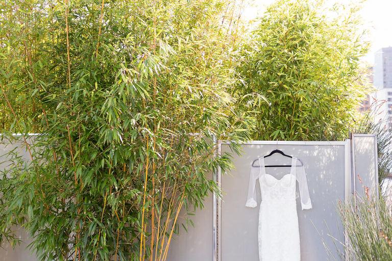 Monique's wedding dress hanging on a gate near bamboo