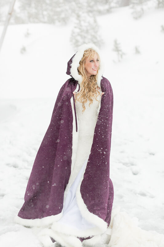 Bride facing the snow while wearing a lined hooded plum cape