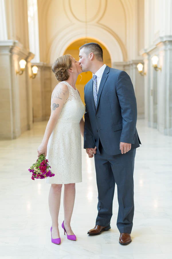 Della and Henry's San Francisco City Hall elopement - kissing and holding flowers