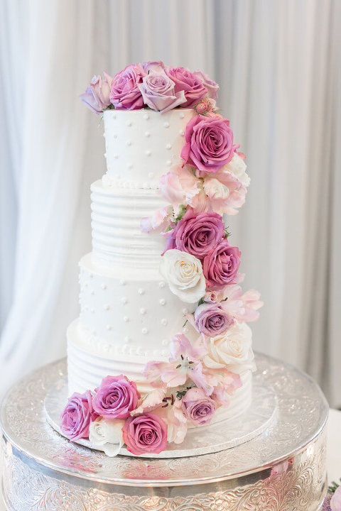 White four tier wedding cake with purple, pink, and white roses