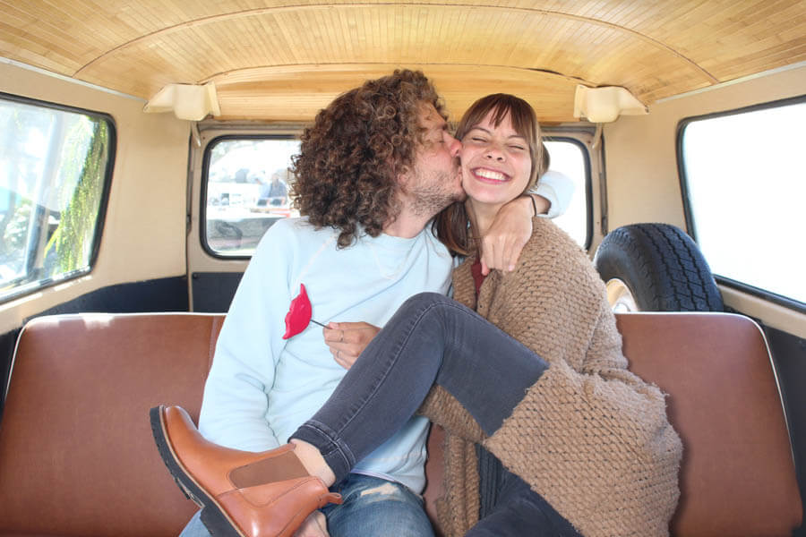 silly couple poses inside vw bus photo booth