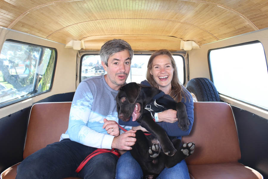 couple with black lab inside vw bus photo booth