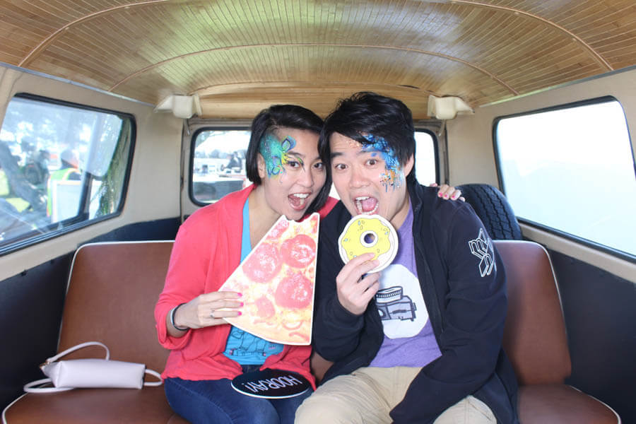 couple with face paint pose with funny food props inside vw bus photo booth