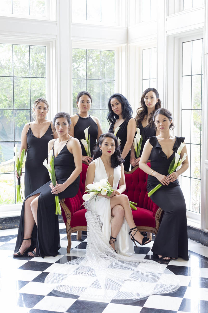 Bride with bridesmaids on checkered floor inside Kohl Mansion
