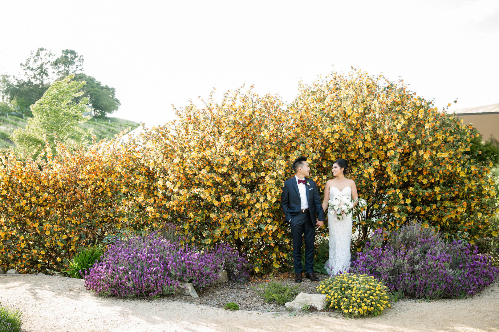 Hellen and Lucas in front of yellow flowers at Nella Terra