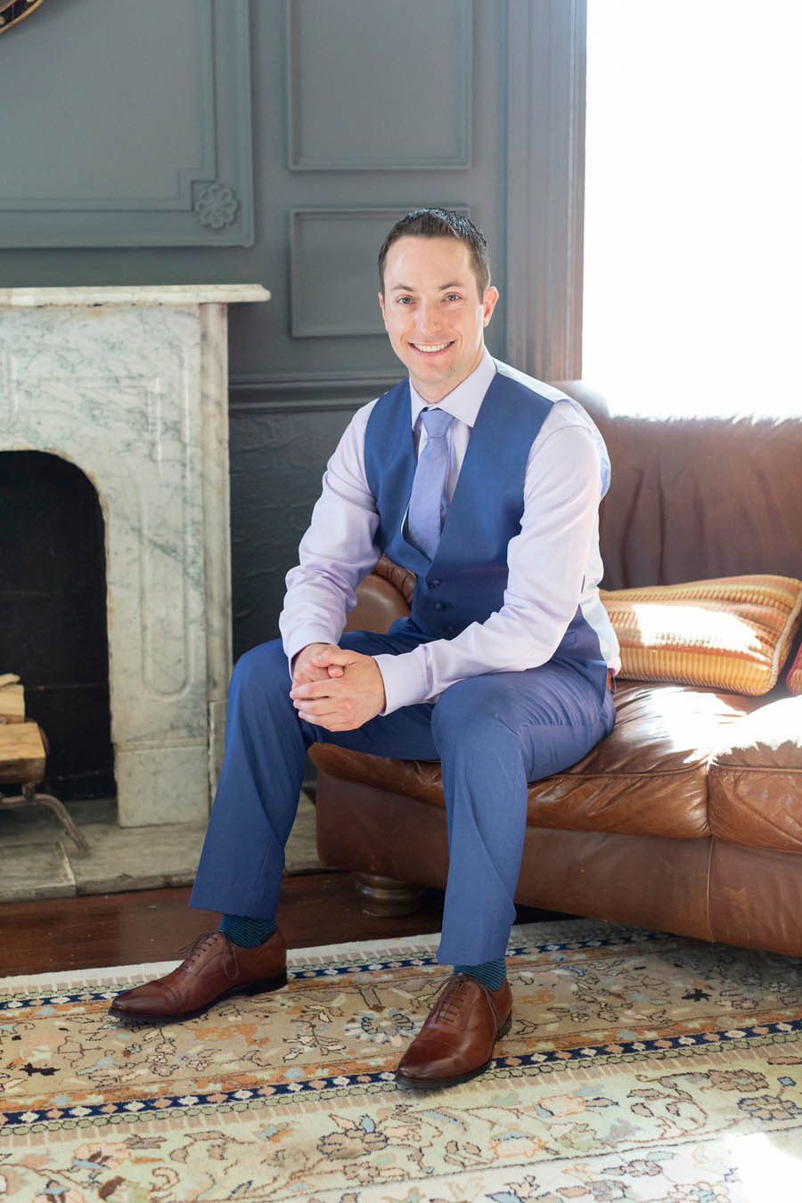 groom sits in front of fireplace