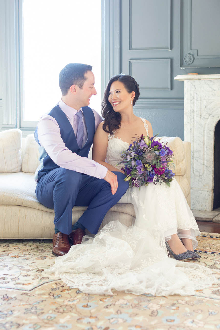 bride and groom smile at each other in front of fireplace