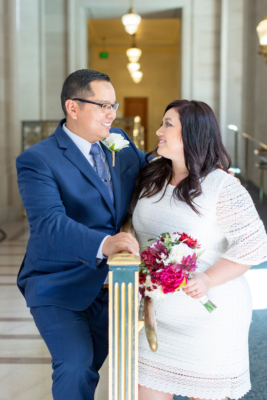 bride and groom lean on railing inside SF City Hall