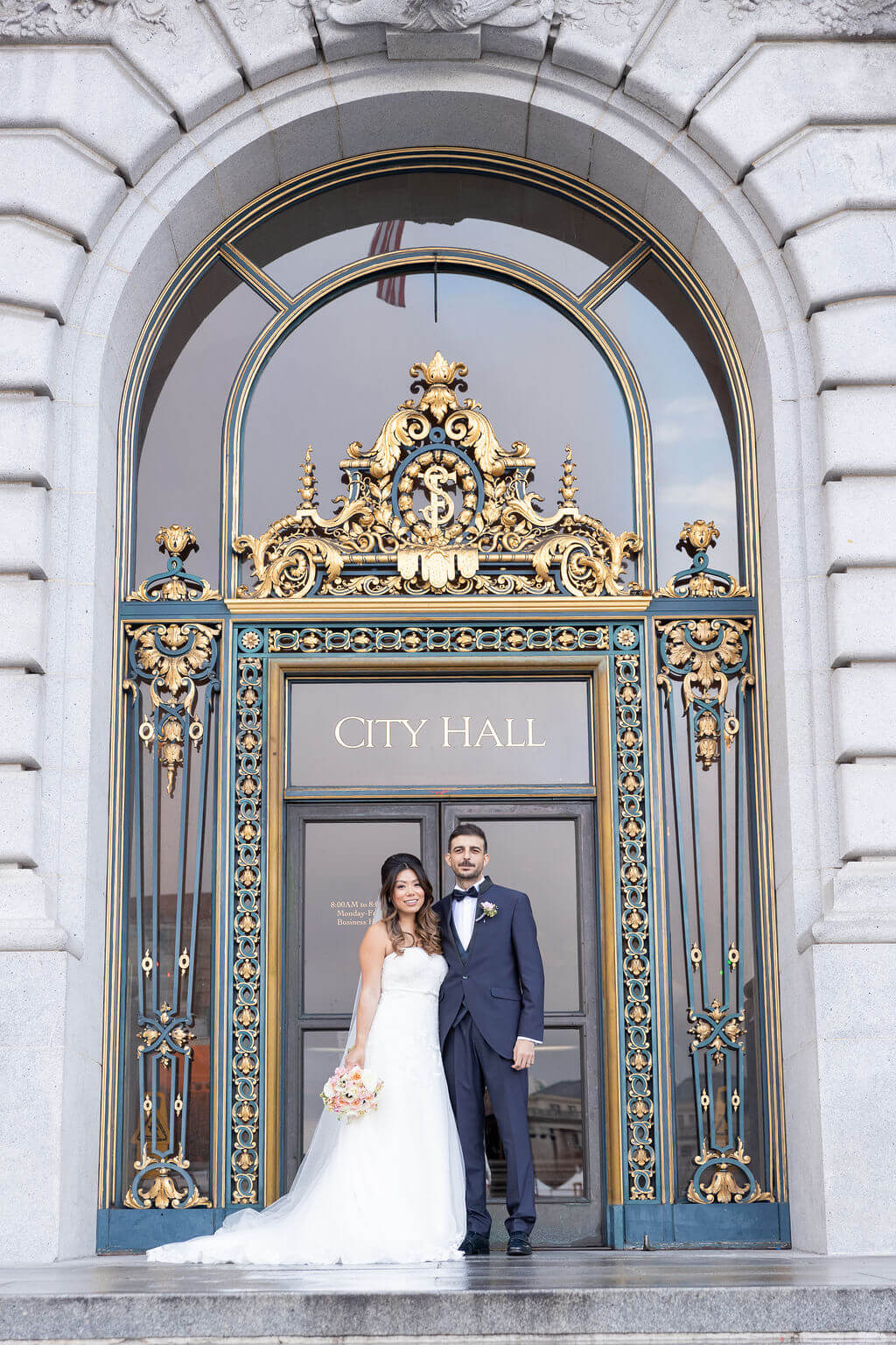 Couple just married stands in front of San Francisco City Hall entrance door