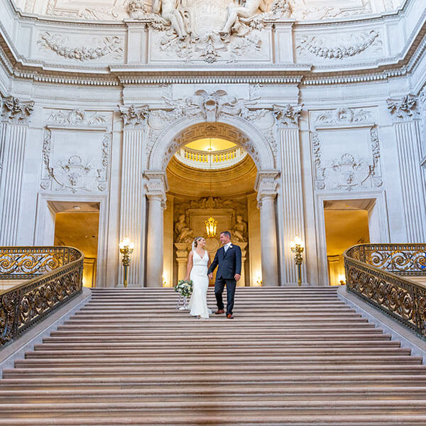 bride and groom walk down grand staircase of San Francisco City Hall