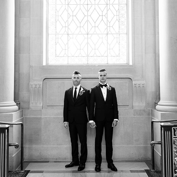 grooms stand in front of window, holding hands