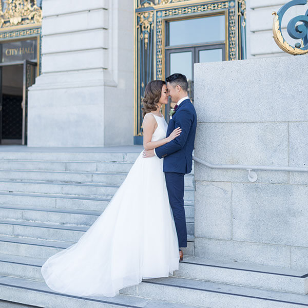 bride and groom on steps outside San Francisco City Hall