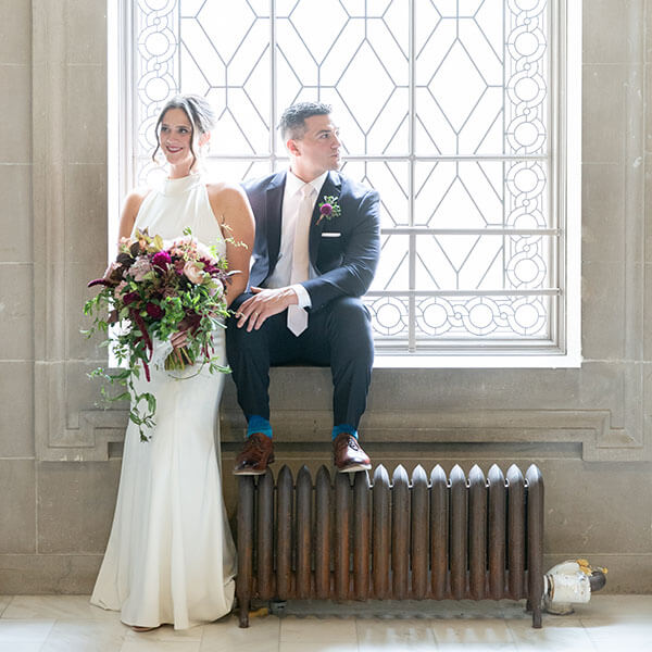 bride and groom pose on radiator inside San Francisco City Hall
