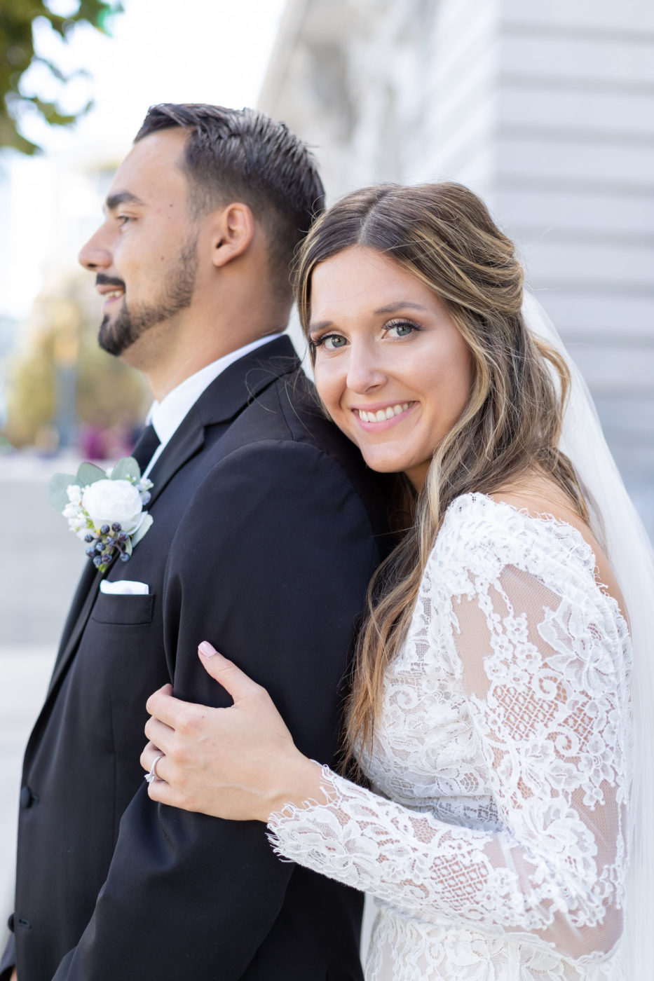 bride stands behind groom with hand lovingly holding arm