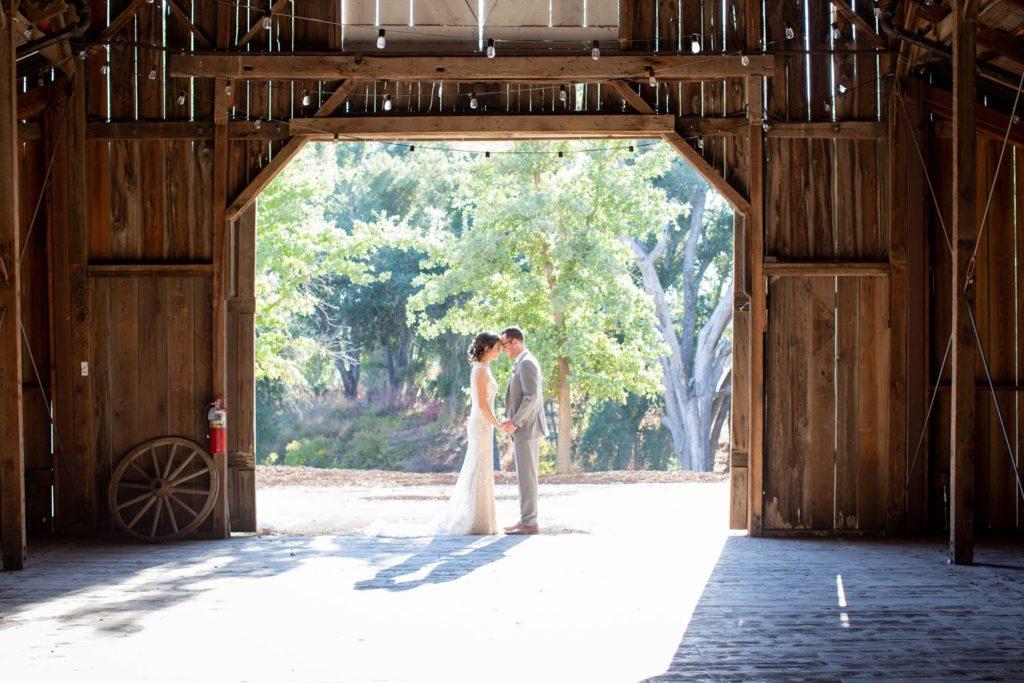 bride and groom in barn doorway
