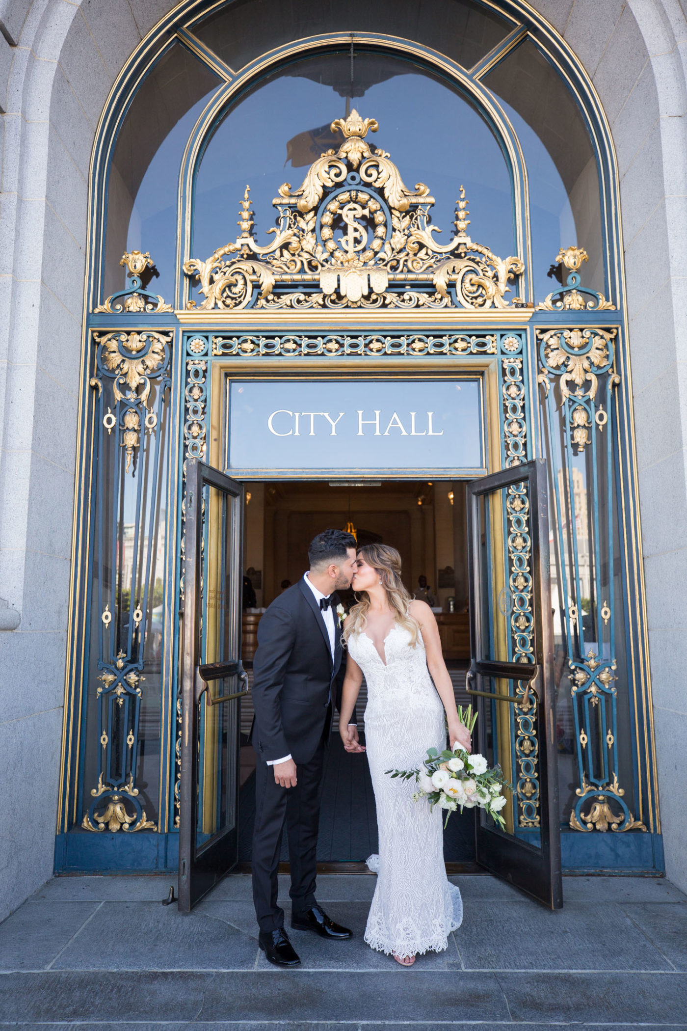 bride and groom kiss outside San Francisco City Hall entrance