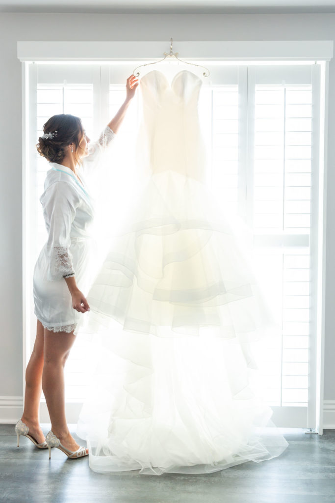 Daniela admires gown hanging in front of window - getting ready