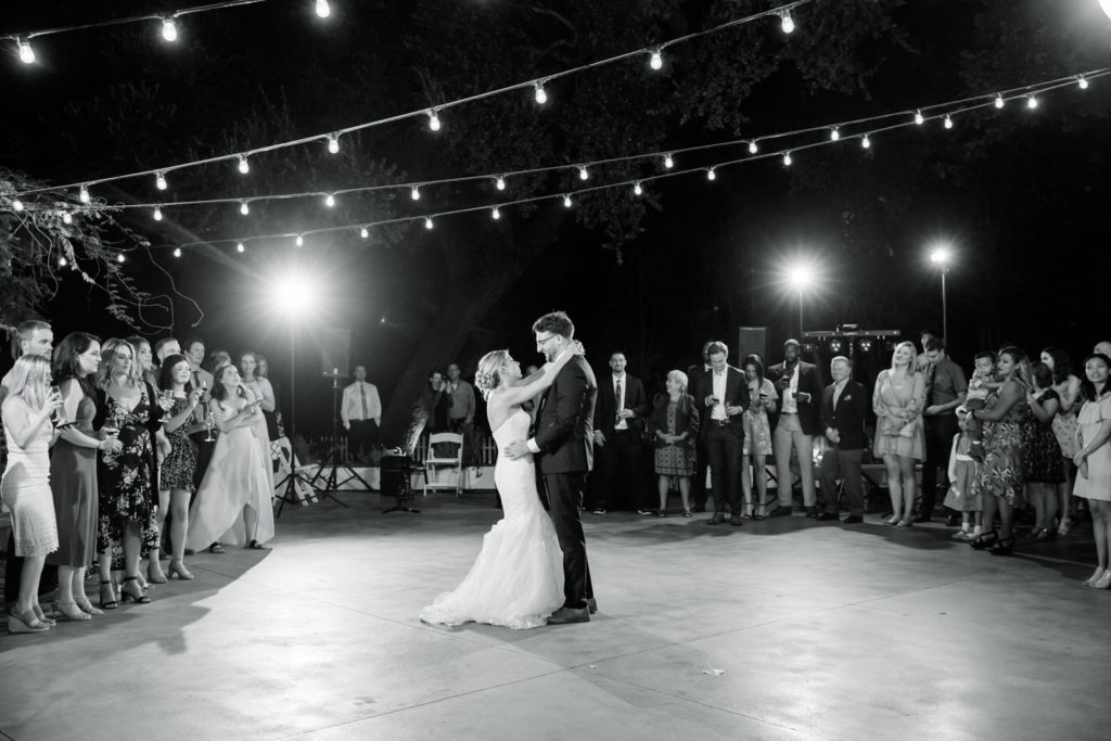 black and white photo of bride and groom dancing under lights