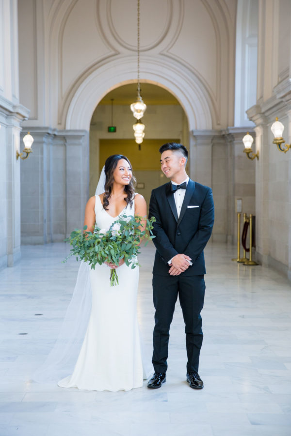 bride and groom smile at each other inside San Francisco City Hall