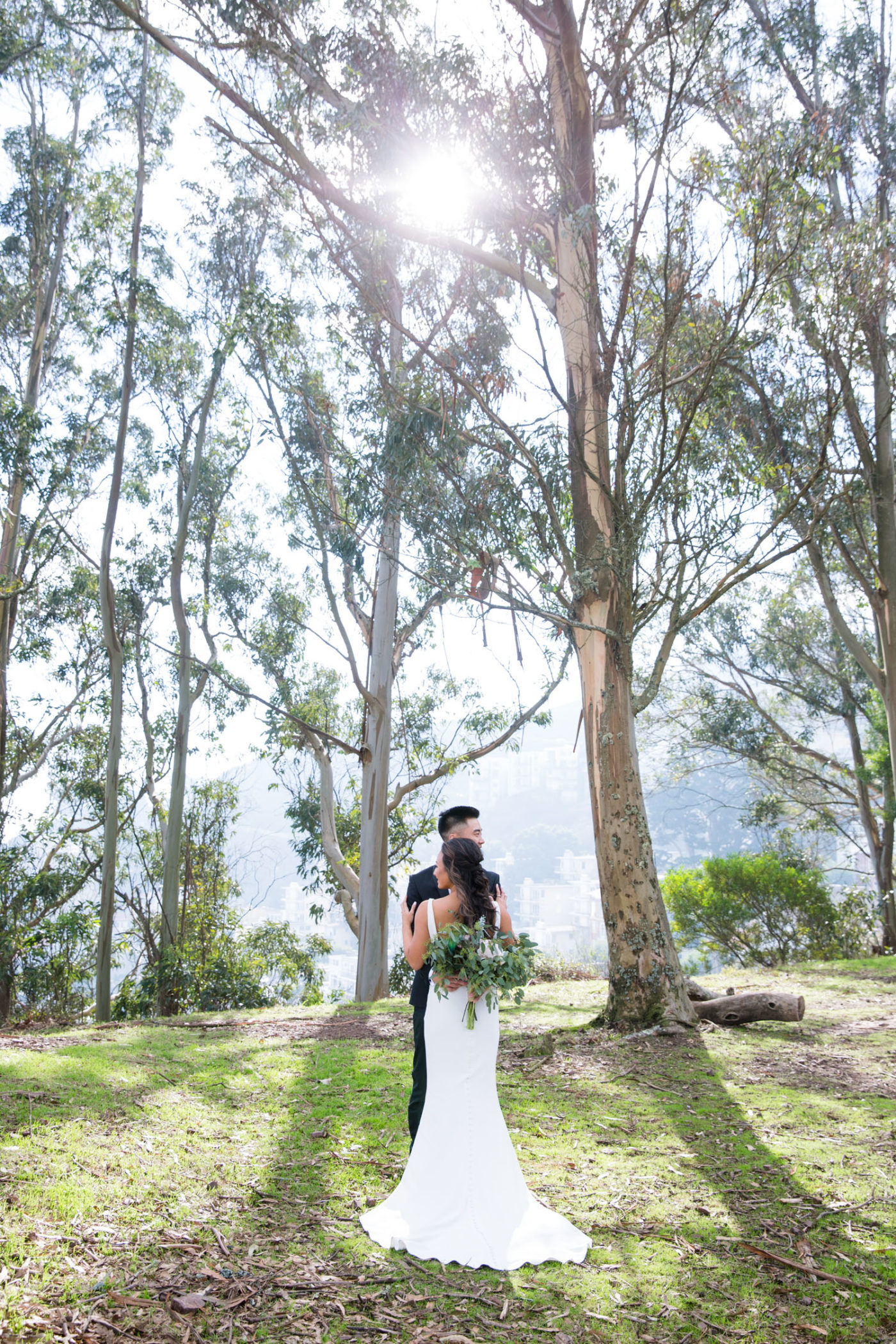 bride and groom embrace under the trees near the ocean