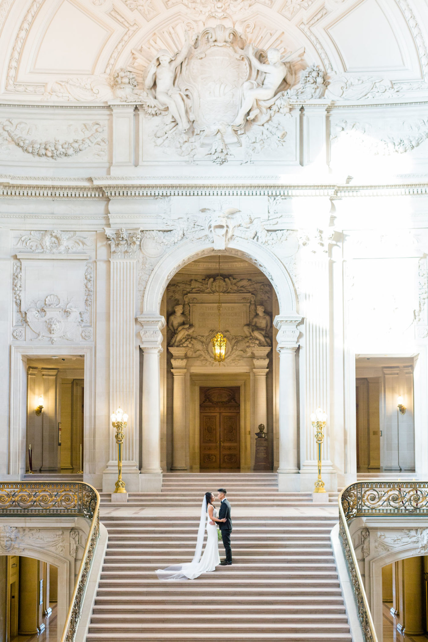 bride and groom on grand staircase of San Francisco City Hall
