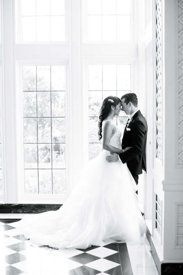 black and white photo - bride and groom lean against wall