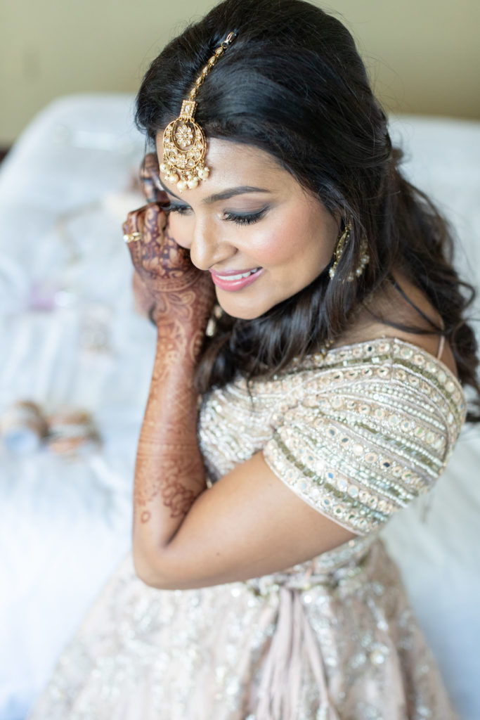 Indian bride putting earring in